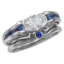 Carved Curls Engagement Ring with Oval Diamond and Tapering Blue Sapphires