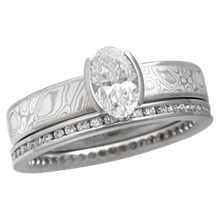 Mokume Solitaire Straight Tapered Engagement Ring with an Oval Diamond and Diamond Channel Brilliant Eternity Band